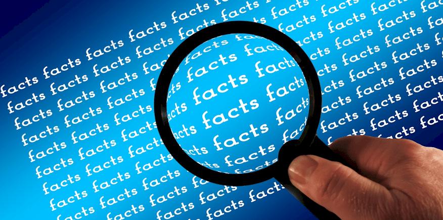 """Symbolbild: Durch eine Lupe betrachtet: """"Fakten, Fakten, Fakten"""""""