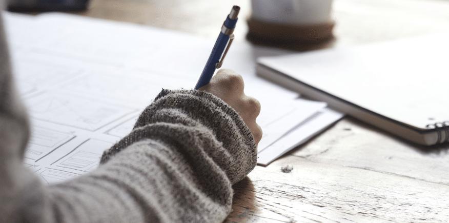 Symbolbild für schriftliche AEVO-Prüfung: Hand mit Kugelschreiber auf einem Schriftstück