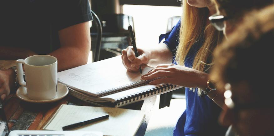 Symbolbild: Hand einer jungen Frau; sie schreibt mit einem Kugelschreiber.
